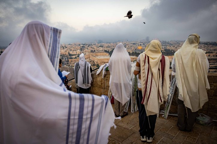 Jewish men covered with prayer shawls pray for rain overlooking Jerusalem's Old City (Yonatan Sindel/Flash90)